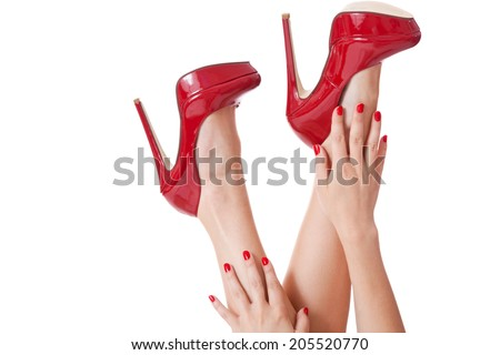 Close up view of the hands of a sensual sexy woman in red stilettos and matching nail varnish caressing her legs as she kicks her feet in the air in a provocative pose, isolated on white - stock photo
