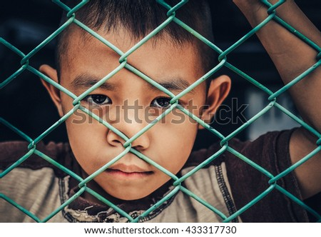 Close up view of the of a stray little boy sad behind the corral of refuge.Portrait of Upset boy at the day time.Sadly children stayed behind Steel wire mesh.
