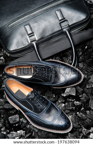 Close-up view of the stylish and elegant black leather men's dress shoes and a bag for business meetings. - stock photo