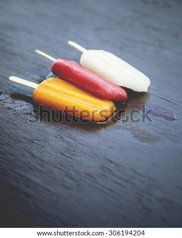 Close-up view of three refreshing, melting, popsicle cold pops on a rustic wooden table. Flavors of raspberry, peach, and lemon, shallow DOF - stock photo