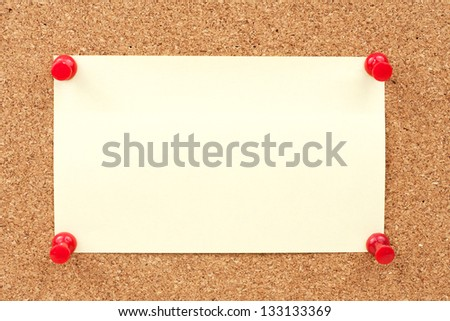 close up view of thumbtacks and note pinned on corkboard