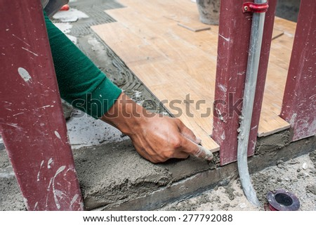 Close-up view of tiler hands fixing tile with spacers at construction  work - stock photo