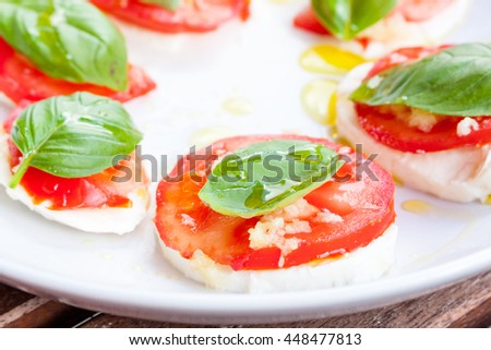 Close-up view of tomato, mozzarella and basil salad drizzled with olive oil on a white plate
