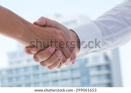 Close up view of two business people shaking hands in the office