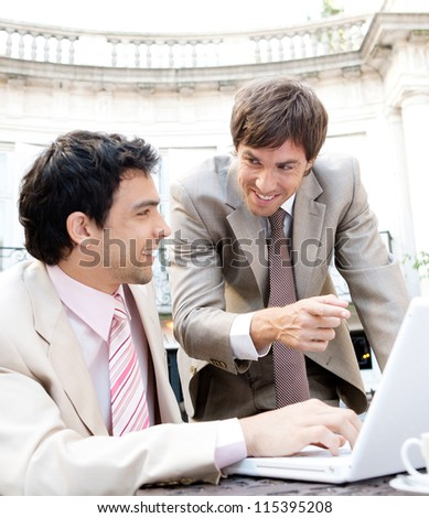 Close up view of two businessmen having a meeting while sitting in a classic coffee shop terrace, using a laptop computer and smiling.