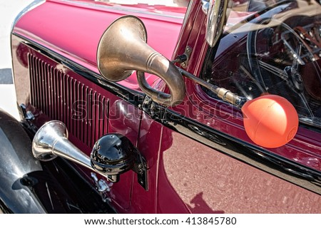 Close up view of two shiny metal horns on red classic car. Sound signal used to avoid traffic accidents. Way of warning or informing people about danger. - stock photo