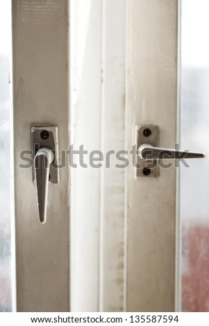 Close up view of two window handles. One of the windows is open, other one closed.