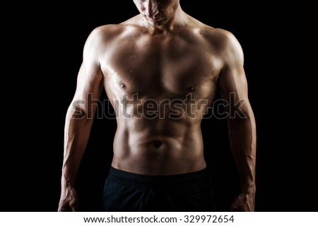 Close up view of very muscular handsome sexy guy isolated on black background, naked torso