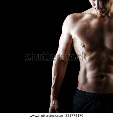 Close up view of very muscular handsome sexy guy isolated on black background, naked torso - stock photo