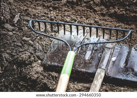 Close-up view of vintage gardening tools on rich, dirt pile, shallow DOF - stock photo