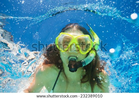 Close up view of woman swimming underwater - stock photo