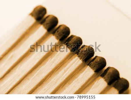 Close-up view of wooden matches in matchbook. Sepia toned - stock photo