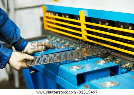 Close-up view of worker's hand at workshop operating guillotine shears machine - stock photo