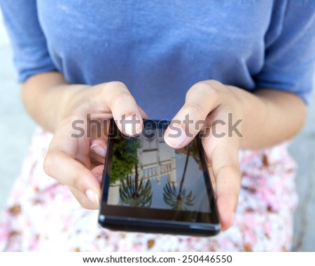 Close up view of young tourist woman hands holding and using a touch screen smartphone mobile cell device, flicking through holiday pictures on vacation. Travel and lifestyle technology outdoors. - stock photo