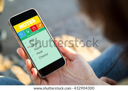 close-up view of young woman checking shopping list on note app. All screen graphics are made up. - stock photo
