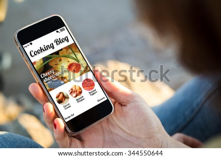 close-up view of young woman holding a smartphone with cooking blog on screen. All screen graphics are made up. - stock photo