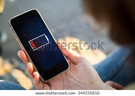 close-up view of young woman holding a smartphone with low battery on screen. All screen graphics are made up. - stock photo