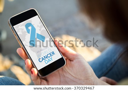 close-up view of young woman looking her mobile phone a World Cancer Day background. All screen graphics are made up.