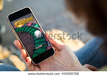 close-up view of young woman playing online casino with her mobile phone. All screen graphics are made up. - stock photo