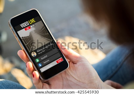 close-up view of young woman watching a live video on her mobile phone. All screen graphics are made up. - stock photo