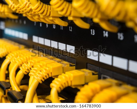 Close-up view on a patch panel with yellow network cables - stock photo