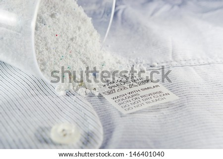 Close up view on an washing label tag and washing powder. - stock photo
