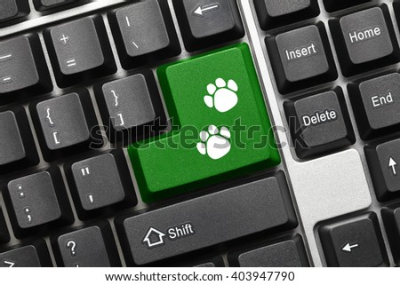 Close-up view on conceptual keyboard - Green key with dog footprints symbol - stock photo
