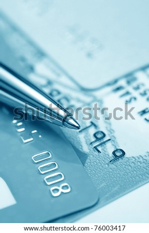 Close up view on credit cards and ballpoint. Business still-life. Blue toned - stock photo