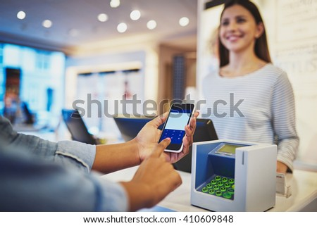 Close up view on fingers of customer entering information on phone in front of register as female cashier smiles in store - stock photo
