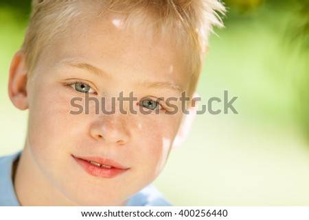 Close up view on handsome little blond boy with hazel colored eyes in front of obscured green outdoor background