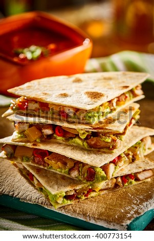 Close up view on stack of four delicious wheat tortilla quesadillas filled with meat, avocado, peppers and cheese with salsa bowl - stock photo