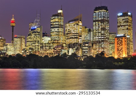Close-up view on tall modern towers of Sydney city business district at sunset when office windows are brightly illuminated reflecting in blurred waters of harbour - stock photo