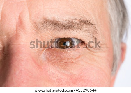 Close-up view on the eye of senior man. Horizontal photo - stock photo