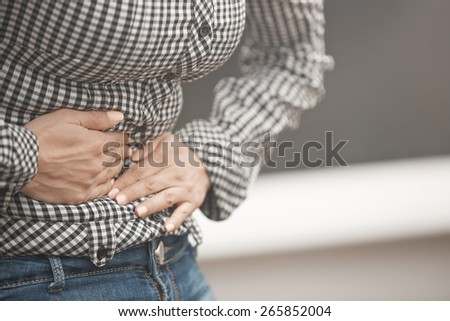 Close-up view on the woman torso suffering of stomach ache - stock photo