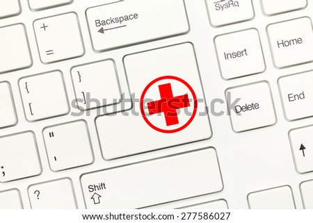 Close-up view on white conceptual keyboard - Key with Red Cross symbol