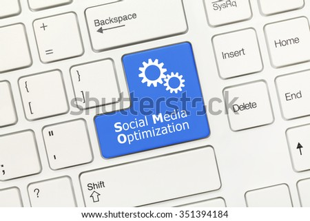 Close-up view on white conceptual keyboard - Social Media Optimization (blue key with gear  symbol) - stock photo