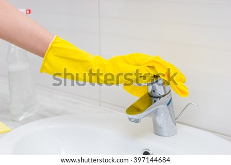 Close up view on yellow rubber gloved hand cleaning chrome sink spigot with soft cloth beside clear spray bottle in bathroom - stock photo