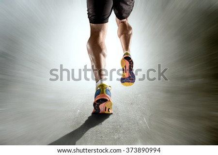 close up view strong athletic legs with ripped calf muscle of young sport man running isolated on motion grunge background in sport fitness endurance and high performance concept - stock photo