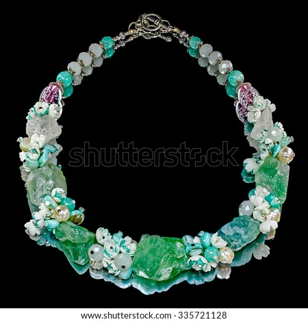 Close-up view to handmade necklace with a large fluorite, quartz, faceted glass beads, agate, freshwater pearls and small flowers from foamiran (artificial suede)Some flowers toned in pale green - stock photo