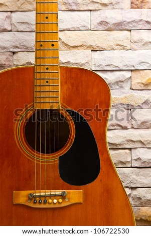 close up vintage acoustic guitar on sand stone wall