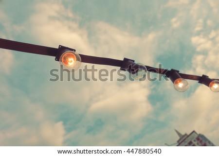 Close up vintage light bulbs against blue sky. filter color tone   - stock photo
