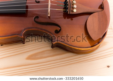Close up violin on pine wood table.