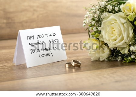 Close up Wedding Greeting Card with May You Two Always Stay Together In Love Message, Bouquet of Fresh White Flowers and a Pair of Rings on Top of a Wooden Table. - stock photo