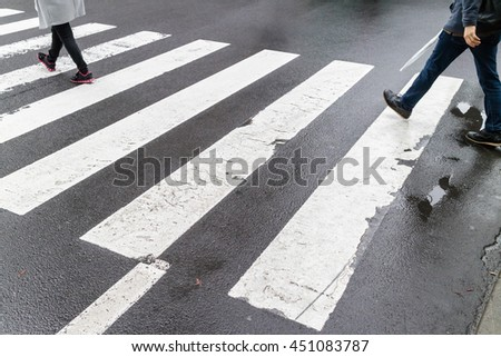 Close up wet crosswalk and walking step on city street, safety concept.
