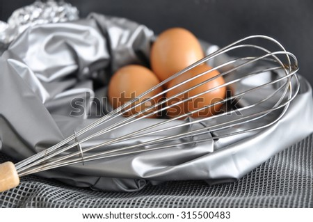 close up whisk with eggs on silver background