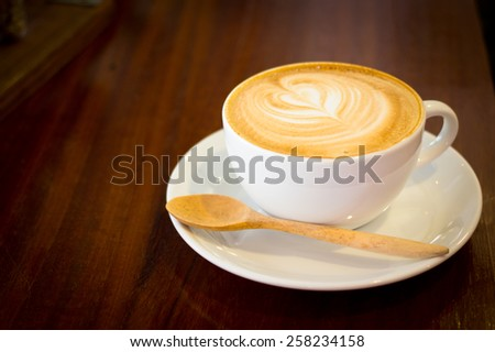 Close up white cup of cappuccino stands on dark wooden table - stock photo