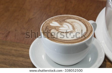 Close up white cup of Coffee, latte on the wooden table - stock photo
