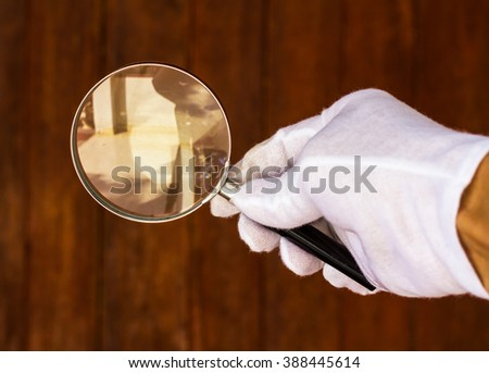 Close up white gloved hand to hold the magnifying glass room with old wooden walls as a backdrop. - stock photo