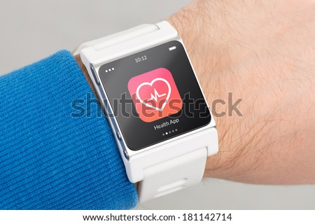 Close up white smart watch with health app icon on the screen is on hand - stock photo