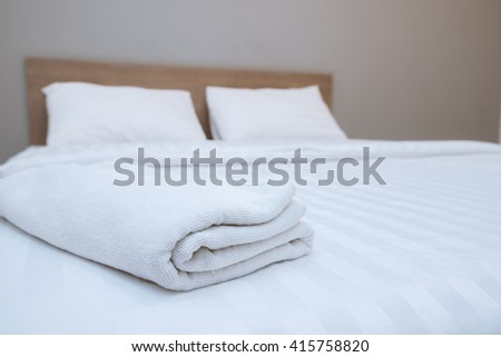 Close up white towels lying on the bed